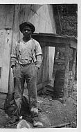 Black Man Standing in Front of Barn
