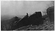 Man Sitting on Rock - Mountains in Background