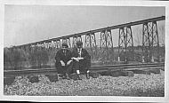 Two Men Sitting on Railroad Tracks